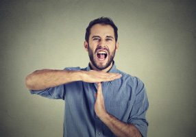 Young man showing time out hand gesture, frustrated screaming to stop isolated on grey wall background. Too many things to do overwhelmed. Human emotions face expression reaction
